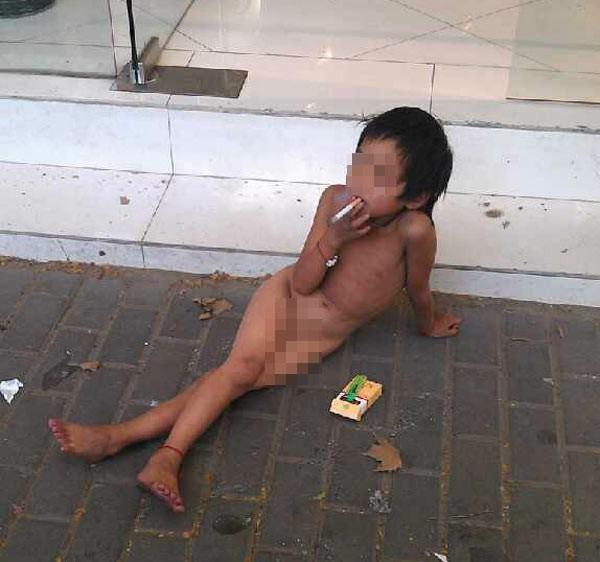 Bố bắt con gái 6 tuổi trần truồng, hút thuốc lá xin ăn 1